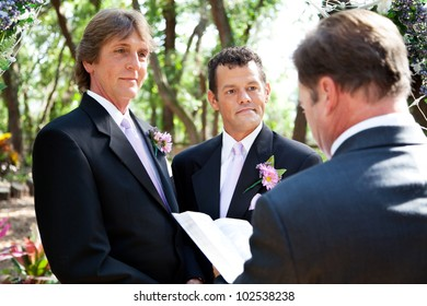 Handsome gay male couple getting married by a minister in beautiful outdoor setting.