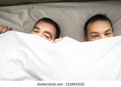 A Handsome gay men couple on bed together under the cover