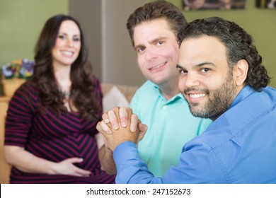 Handsome gay men holding hands with smiling surrogate mother