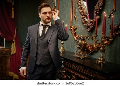 Handsome gentleman poses in a tweed suit and glasses in a vintage interior. Luxurious lifestyle. Vintage style.