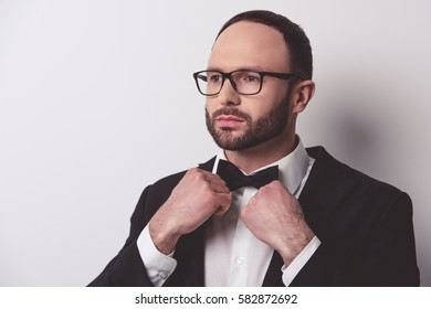 Handsome gentleman in suit and eyeglasses is adjusting his bow tie, on gray background