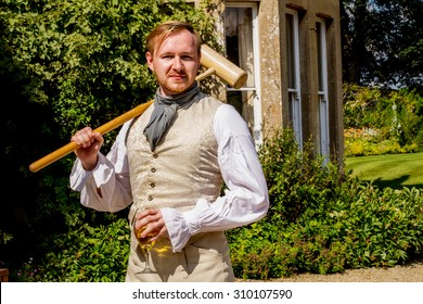 Handsome ginger hair man dressed in regency period costume with glass of sparkling vine and croquet mallet. Image with selective focus
