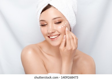 handsome girl in bath towel and naked shoulders applying cream on her cheek looking down, woman with pure clean skin moisturizing face