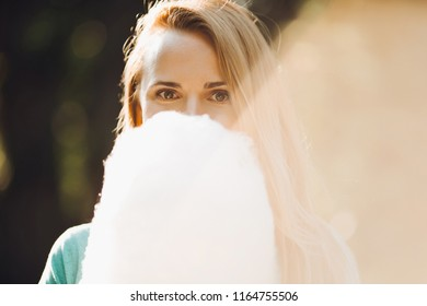 Handsome girl holding candyfloss in her hand and eating it. Adorable lady wearing flowery red dress and with chestnut hair posing with cotton candy. Background of city park.