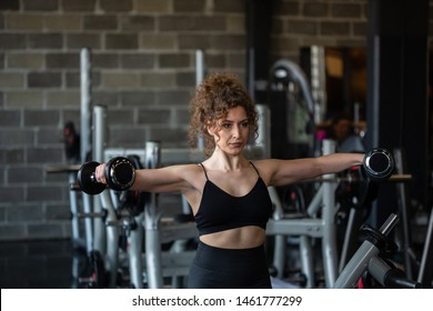 Handsome girl lifting weights in gym