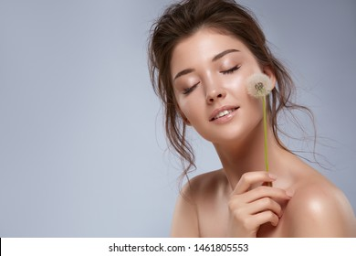 handsome girl with naked shoulders and eyes closed holding dandelion near her cheek, sensetivy woman with nude make-up and flower in her hand