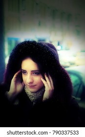 A handsome girl is standing in a street. It is winter time and it is snowing. She is wearing a coat with a hood and a scarf. Trying to hide her hair under the hood. She has long brown hair.