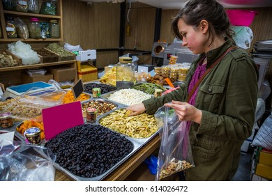 handsome girl tourist chooses various colored spices on the Mahane Yehuda Market in Jerusalem, israel