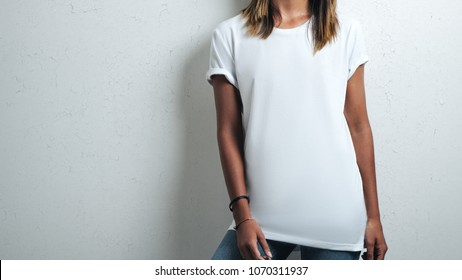 Handsome girl in white blank t-shirt, grunge wall, studio close-up