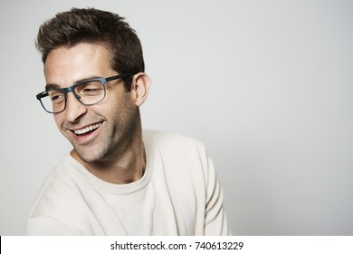 Handsome glasses guy laughing in studio