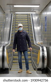 Handsome good looking, attractive Caucasian man wearing navy blue jacket, jeans, tweed flat cap and surgical mask step down from escalator in underground station London, United Kingdom