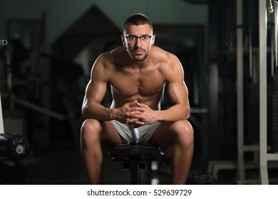 Handsome Good Looking And Attractive Young Man In Glasses With Muscular Body Relaxing In Gym