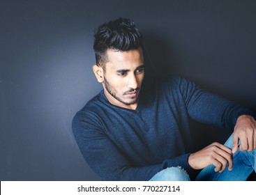 A handsome and good looking indian or arab male model with dark eyes and dark hair and a small beard, is posing in a navy blue wool sweater and a blue denim in front of a dark background