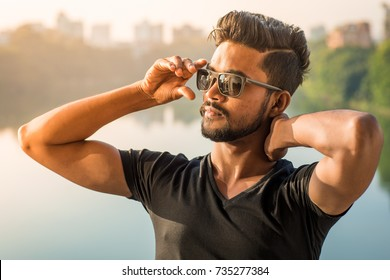 Handsome and good looking indian hunk with an attractive face and fashionable and trendy hair, is standing in a black tshirt on a balcony overlooking the lake during a sunny summer afternoon