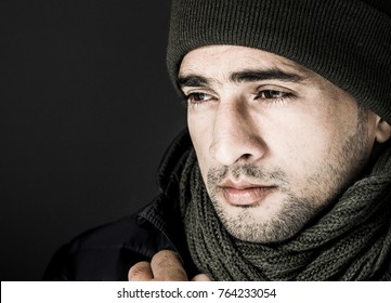 Handsome and good looking sexy male model with a rough and tough look and sharp facial features, is posing for a winter shoot in studio with a navy blue jacket and a green shawl and a black background