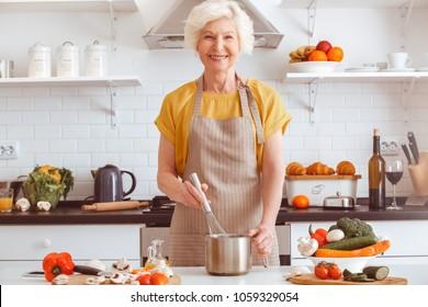Handsome grandma cooking veggie dinner, toothy smiling
