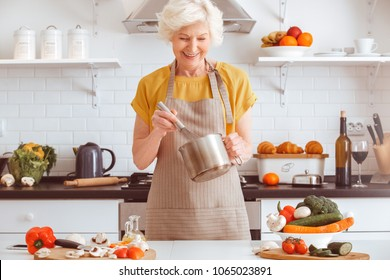 Handsome grandma cooking veggie dinner, toothy smiling, making veggie mayo