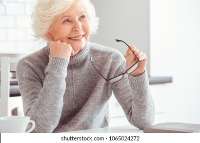 Handsome grandma holding eyeglasses and dreaming