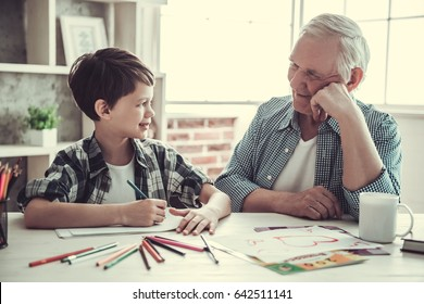 Handsome grandpa and grandson are looking at each other and smiling while spending time together at home. Boy is drawing