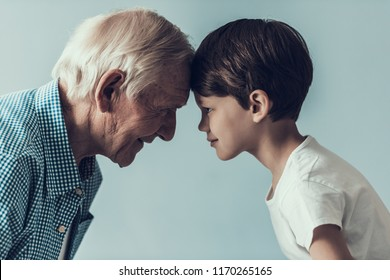 Handsome Grandpa and Grandson on Blue Background. Happy Grandfather and Grandson Looking at Each Other. Family, Generation, Relations and People Concept. Lifestyle Parenting Childhood Values Weekend.