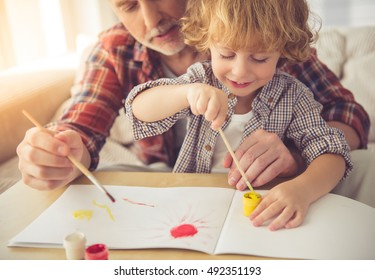 Handsome grandpa and grandson are painting using gouache and smiling while spending time together at home