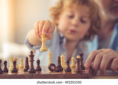 Handsome grandpa and grandson are playing chess while spending time together at home. Little hand holding chess piece in focus