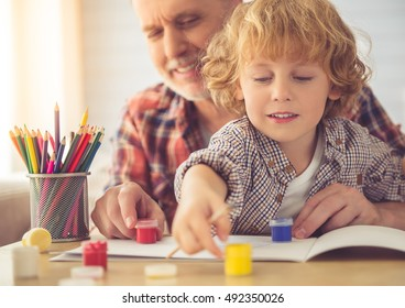 Handsome grandpa and grandson are smiling while drawing together at home