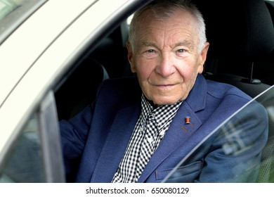 Handsome gray haired senior man dressed in business casual driving car looking into camera