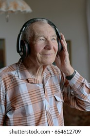 Handsome gray haired senior man with headphones listening to music in the living room