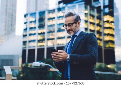 Handsome gray haired smiling businessman with trendy haircut in black coat and blue tie in glasses texting on smartphone by glass fence on blurred background in New York