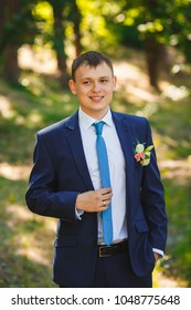 Handsome groom in blue suit is standing in sunny forest.