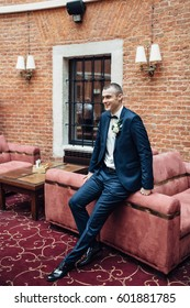 Handsome groom in dakr blue suit leans on red sofa in old brick hall