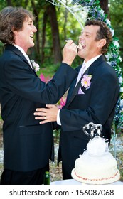 Handsome groom feeds his new husband wedding cake at their reception.