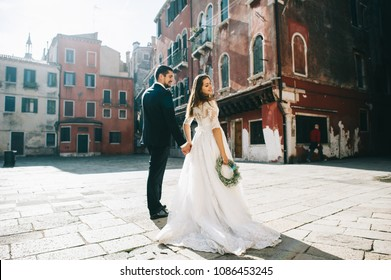 Handsome groom kissing happy bride in street