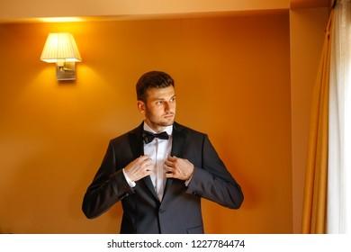 Handsome groom preparing for wedding. Ceremony, button.