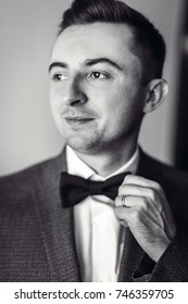 Handsome groom puts on jacket standing in the room
