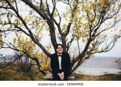 The handsome groom sits on the bench