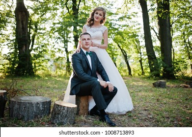 Handsome groom sitting on a stump while bride standing beside him in the forest.