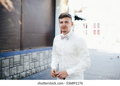 The handsome groom stands near building