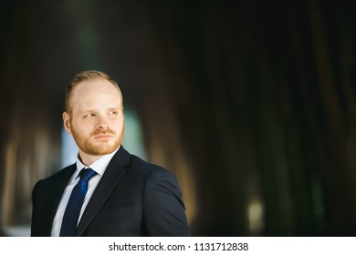 The handsome groom stands in the park