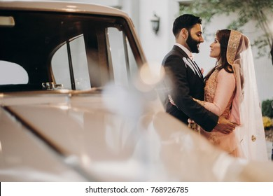Handsome groom and stunning Indian bride in pink sari stand before a white retro car