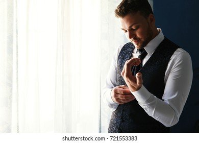 Handsome groom in stylish blue waistcoat stands before a window and fixes his cufflinks