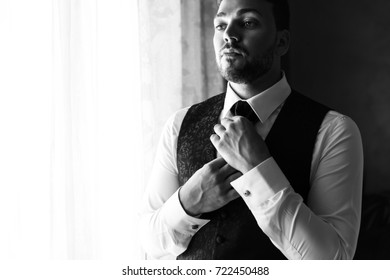 Handsome groom in stylish blue waistcoat stands before a window and fixes his tie