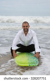 Handsome groom surfing at the beach during summer