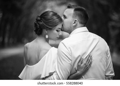 Handsome groom tenderly kissing his beautiful wife on a walk in the park