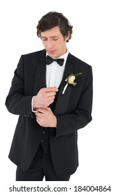 Handsome groom in tuxedo adjusting cuff link on white background