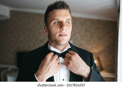 The handsome groom wears a wedding butterfly