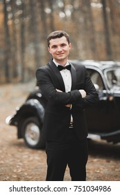 Handsome groom at wedding smiling and waiting for bride near retro car