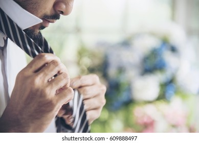 Handsome groomsman wear tie preparing to be best man for groom in a wedding day. Formal suit. Wedding concept