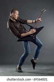 Handsome guitarist playing his electric guitar on black background